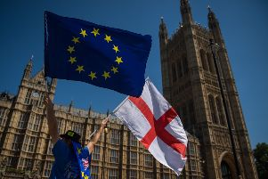 An anti-Brexit demonstrator holds European Union and England flags outside the Houses of Parliament. Picture: PA