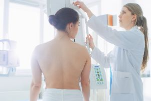 A doctor adjusts a mammogram machine for a female patient