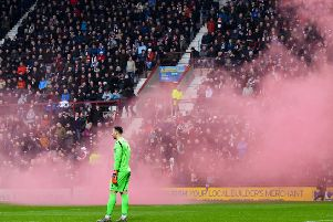 Ofir Marciano watches after a smoke bomb is let off at the side of the pitch. Pic: SNS/Craig Williamson