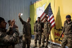 American-backed forces celebrate victory against Isis in Baghouz, Syria, with a selfie. Picture: Chris McGrath/Getty