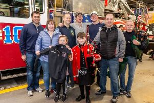 Piper Josh Bruce with his personalised jacket from the New York Fire Department. Picture: New York Tartan Week/PA