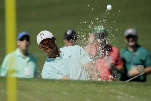 Tiger Woods hits out of the bunker on the second hole during practice. Picture: Charlie Riedel/AP