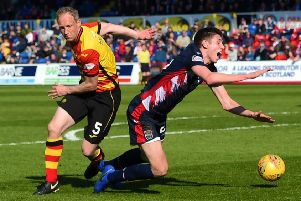 Ross County's Ross Stewart goes down under a challenge from Partick Thistle's Steven Anderson. Pic: SNS/Paul Devlin