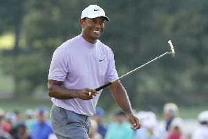 Tiger Woods smiles as he walks on the 18th hole during the third round at Augusta National. Picture: Getty Images
