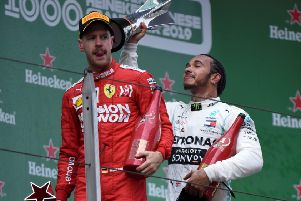 Lewis Hamilton celebrates with the trophy but Sebastian Vettel edured a difficult afternoon. Picture: AFP/Getty