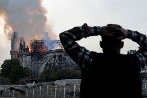 A man watches the landmark Notre-Dame Cathedral burn, engulfed in flames, in central Paris on April 15, 2019. (Photo by Geoffroy VAN DER HASSELT / AFP)