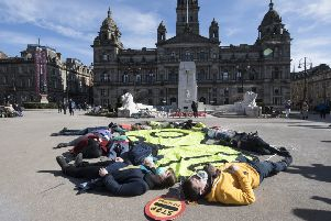 Air pollution protesters wearing gas masks stage a 'die-in' in Glasgow's George Square (Picture: John Devlin)