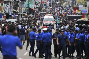 Sri Lankan police officers clear the road as an ambulance drives through carrying injured of Church blasts in Colombo, Sri Lanka. (AP Photo/Eranga Jayawardena)