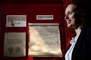 Abby Richards inspects the Edward I's English exchequer pipe roll from 1305, which reveals details of Sir William Wallace's execution. Picture: Mike Day/Saltire News
