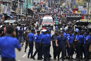 Sri Lankan police officers clear the road as an ambulance drives through carrying injured of Church blasts in Colombo. Picture: AP/Eranga Jayawardena)