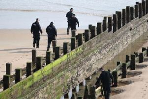 Police examining the beach where the women died. Picture: PA