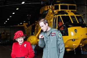 Prince William with his grandmother the Queen during his time as an air ambulance pilot. Picture: Getty