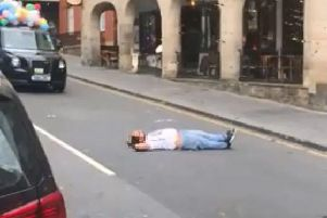 The man laid in th emiddle of the road so the parade couldn't pass