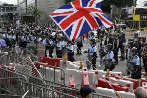 A man waves a British flag as policemen in anti-riot gear stand guard against the protesters in Hong Kong. Picture: AP