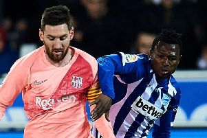 Patrick Twumasi (right) tussles with Lionel Messi