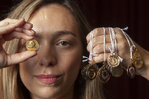 Hannah Murphy from McTear's Auctioneers with a European Cup Winner's Cup finalist medal (left) and other footballing medals, won by Rangers captain Bobby Shearer.