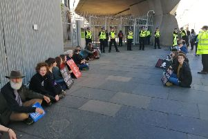 Extinction Rebellion protestors glue themselves to sites around the Parliament building at Holyrood