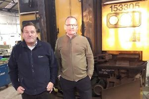 Jim Thomson and Stephen Birnie at Brodie Engineering standing in front of a Class 153 train awaiting refurbishment for ScotRail.
