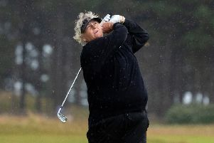Laura Davies hits an iron shot on her way to a three-under-par 68 in the worst of the weather. Picture: Kenny Smith.