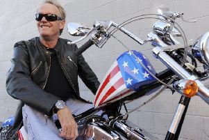 "FILE - In this Friday, Oct. 23, 2009 file photo, Peter Fonda, poses atop a Harley-Davidson motorcycle  in Glendale, Calif. Fonda, the son of a Hollywood legend who became a movie star in his own right both writing and starring in counterculture classics like ""Easy Rider,"" has died. His family says in a statement that Fonda died Friday, Aug. 16, 2019, at his home in Los Angeles. He was 79. (AP Photo/Chris Pizzello, File)"