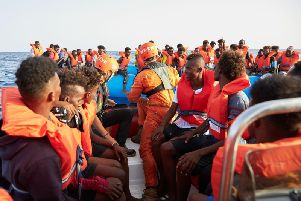 German migrant rescue charity NGO Sea-Eye helping people to get off an overloaded boat in July. Picture: Getty Images
