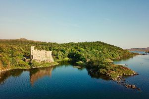 The castle is on the edge of a loch.