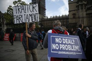 Brexit supporters hold placards outside the Houses of Parliament