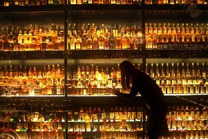 A member of staff looking at the Diageo Claive Scotch Whisky collection. Picture: PA