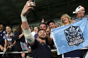 Ryan Wilson takes a selfie with fans after the game