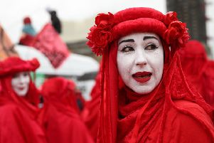 Climate change activists from the group Extinction Rebellion, dressed in red costume, demonstrate in London (Picture: Isabel Infantes/AFP/Getty Images)