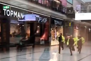 A video grab shows police running through the Arndale Centre in Manchester where at least four people have been treated after a stabbing incident. Picture: @GrizzleMarine /PA Wire