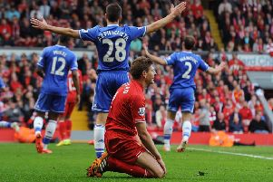 A dejected Steven Gerrard sinks to his knees as Chelsea celebrate their 2-0 victory at Anfield in 2014, a match which had been billed as the league  title decider. Gerrard's slip had led to the Blues' crucial opening goal. Picture: Liverpool FC via Getty