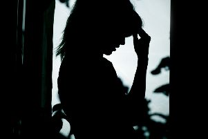 Horizontal woman silhouette in depression, sad girl standing near window in foliage and in desperation put her hand to her head, concept violence in the family,