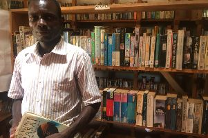 Librarian Burton Chirwa among the thousands of books in his village library in Mwaya (Picture: Susan Dalgety)