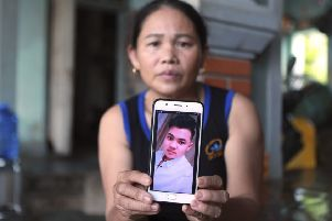 Hoang Thi Ai holds a picture of her son Hoang Van Tiep, feared among the 39 migrants who died in a lorry in Essex (Picture: Hau Dinh/AP)