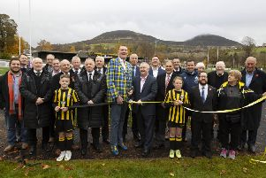 Doddie Weir, in his trademark tartan jacket, unfurls the ribbon to declare the new Greenyards 3G surface at Melrose officially open, with Councillor David Parker, to his left, and representatives of other partners in the project (picture by Brian Sutherland).