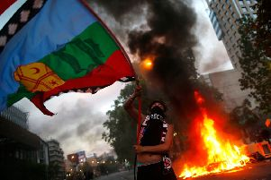 A demonstrator waves a Mapuche indigenous flag near a bonfire in Chile's capital Santiago amid protests over living costs and social inequality (Picture: Pablo Vera/AFP via Getty Images)