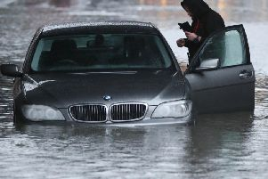 A man with car in a flooded street Sheffield, after torrential rain in the area. Picture: Danny Lawson/PA Wire