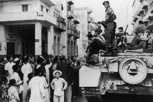 Egyptians crowd around a British tank in Port Said during the Suez Crisis in 1956. (Picture: Fox Photos/Hulton Archive/Getty Images)