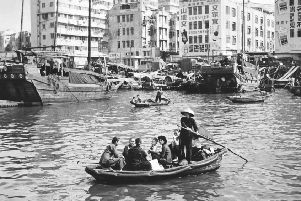 A group of people being ferried across a stretch of water in Hong Kong.  (Photo by Leonard G. Alsford/Fox Photos/Getty Images)