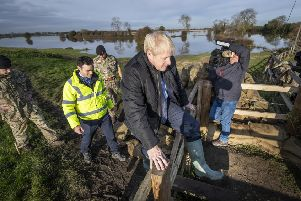 Boris Johnson climbs a stile as he is shown work carried out by the army by Lt Col Tom Robinson from the Light Dragoons and Oliver Harmar, Yorkshire Area Director of the Environment Agency. Picture: Danny Lawson/Getty