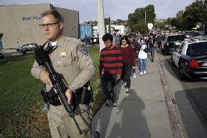 A California Highway Patrol officer escorts pupils out of Saugus High School after a shooting on the campus in Santa Clarita, California (Picture: Marcio Jose Sanchez/AP)