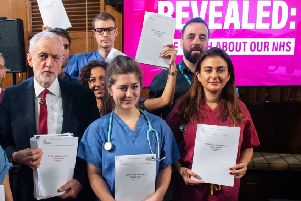 Jeremy Corbyn and NHS staff hold government documents detailing discussions about the NHS in US-UK trade talks (Picture: Dominic Lipinski/PA Wire)