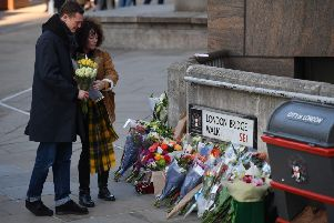 A couple place a bouquet of flowers on London Bridge in memory of the victims of last week's attack (Picture: Daniel Leal-Olivas/AFP via Getty Images)