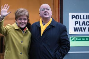 Nicola Sturgeon with husband Peter Murrell as they cast their votes at Broomhouse Park Community Hall today. Picture: PA