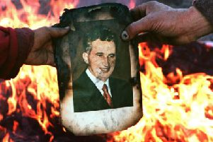 A portrait of Nicolae Ceausescu is burnt in Denta, Romania, as the people rejoice at the dictator's downfall in December 1989. Picture: Joel Robine/Getty