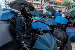 Protesters in Hong Kong hide behind umbrellas so facial recognition technology cannot be used to identify them. Picture: Getty