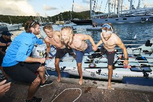 Lachlan, 21, Jamie, 26, and Ewan, 27, (from left to right) celebrate their arrival in Antigua. (Picture: Atlantic Campaigns /SWNS.com)