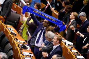 MEP Shaffaq Mohammed of the Renew Europe Group holds up a scarf with the lettering 'United in Diversity' during a vote on the ratification of the Brexit deal