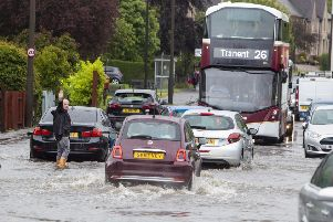A man directs traffic through a flooded road in Barnton, Edinburgh, as heavy rains hit the country last June. Picture: SWNS